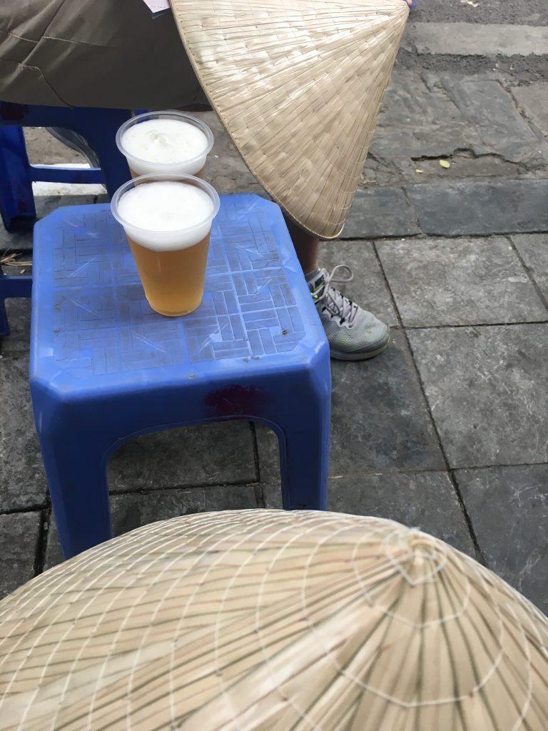 Hanoi in una foto: due nón lá (tipico cappello vietnamita), tre sgabelli e due birre